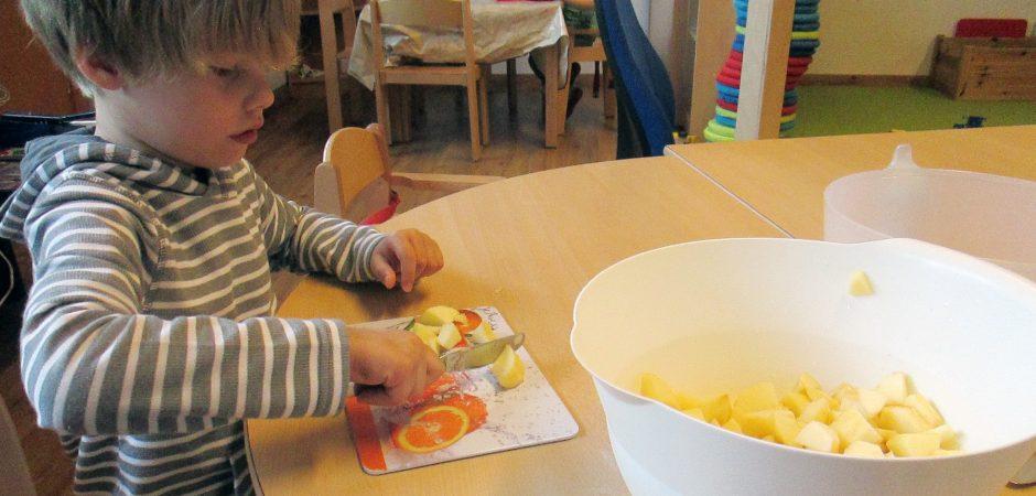 Kindergarten Karlsruhe: Junge schneidet Apfel