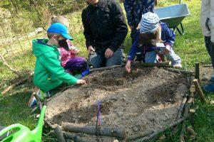 Kinder säen Pflanzen in der Kita Grashüpfer