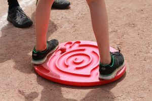 Kind spielt mit einem Slalombrett mit den Füßen