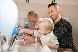 Auszubildender wäscht mit Kindern die Hände