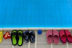 Badeschuhe am Rand eines Schwimmbeckens