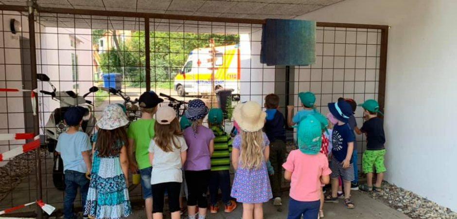 Kinder schauen nach dem Krankenwagen vor der Tür