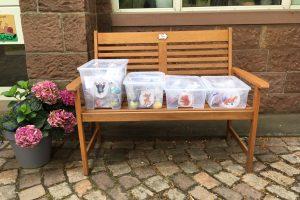 Boxen mit selbstgemachter Knete stehen auf einer Bank