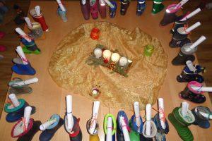 Adventskranz, im Kreis darum Stiefel mit Ausmahlbildern drin
