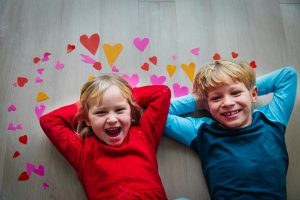 happy cute boy and girl play with hearts from paper, valentine day