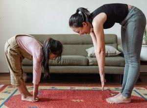 Mädchen und Frau machen Yoga