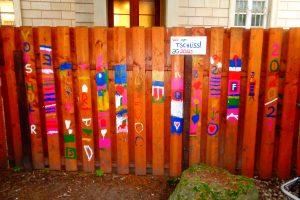 Mit farbigen Buchstaben und Zeichnungen bemalter Holzzaun