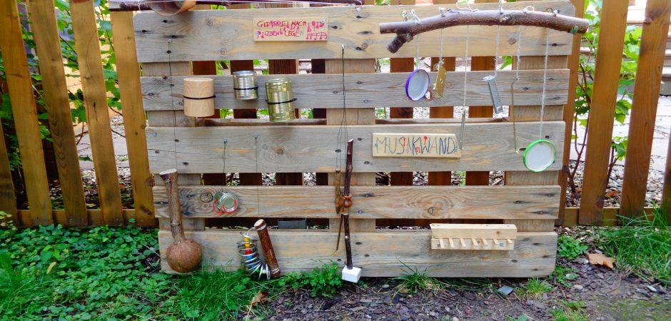 Holzzaun, an dem selbstgemachte Instrumente befestigt sind